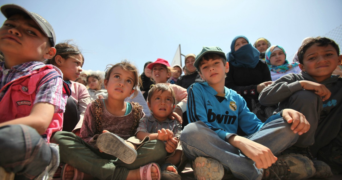 AZRAQ, JORDAN- APRIL 30: Syrian refugee children watch as others perform sports activities in AL- Azraq camp for Syrian refugees on April 30, 2015 in Al-Azraq, Jordan. On the occasion of its first anniversary of opening, the Azraq camp that is located in the desert 110 kilometers to the east of Amman and not far from the Syrian border, UNHCR, Care and other partners innaugurated a multi-purpose sports ground, a souk in the market in the area of village 3, launced the 1st Azraq soccer cup, an open air cinema and other recreational activities for children and adults. (Photo by Jordan Pix/ Getty Images)